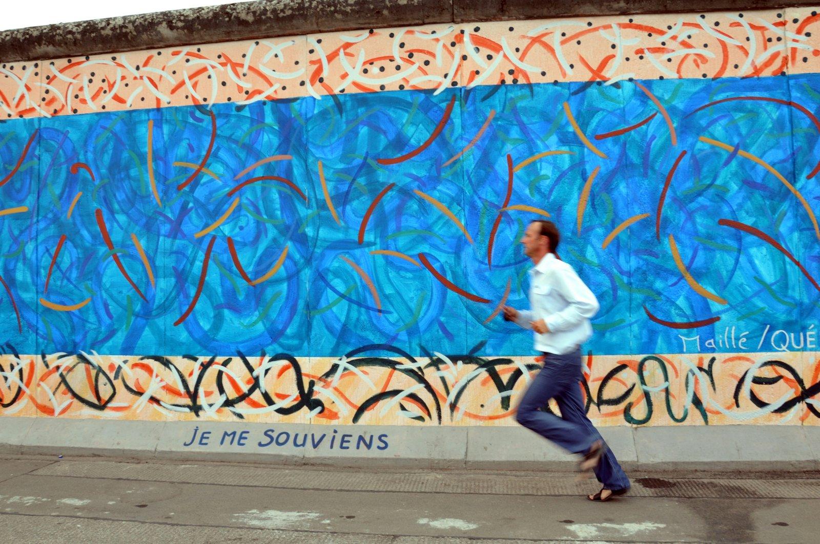 Un homme court devant la East Side Gallery en 2010...