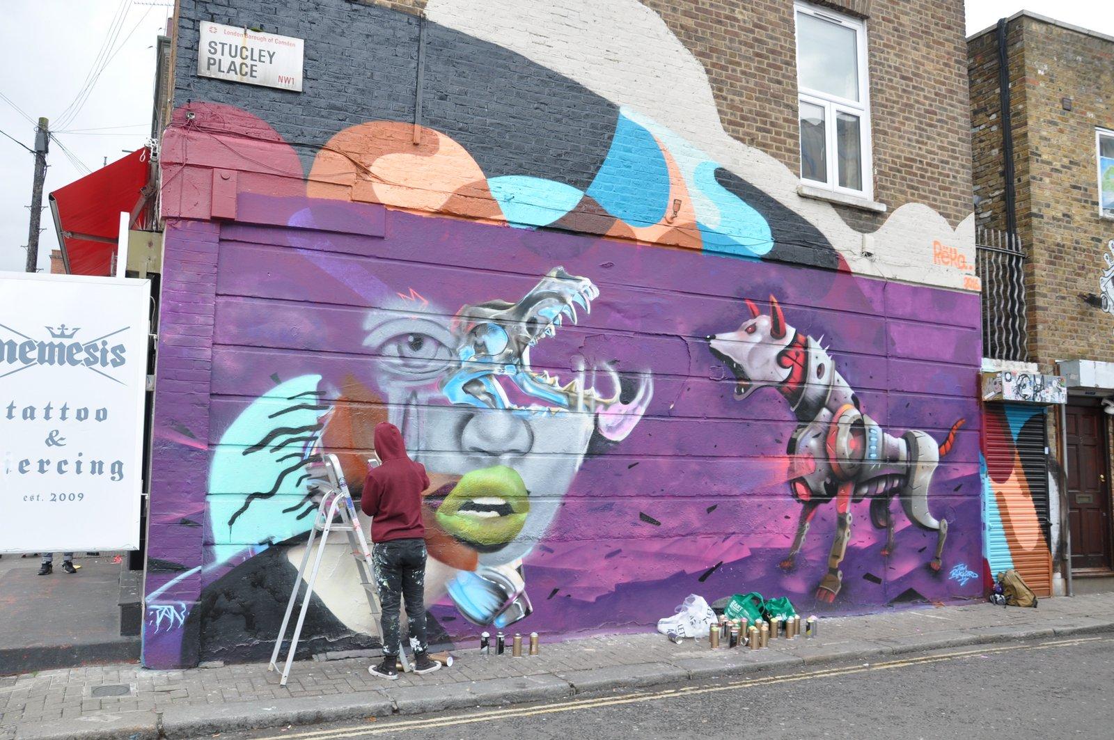 Une fresque de street-art est vite remplacée par une autre... ici un artiste en plein travail