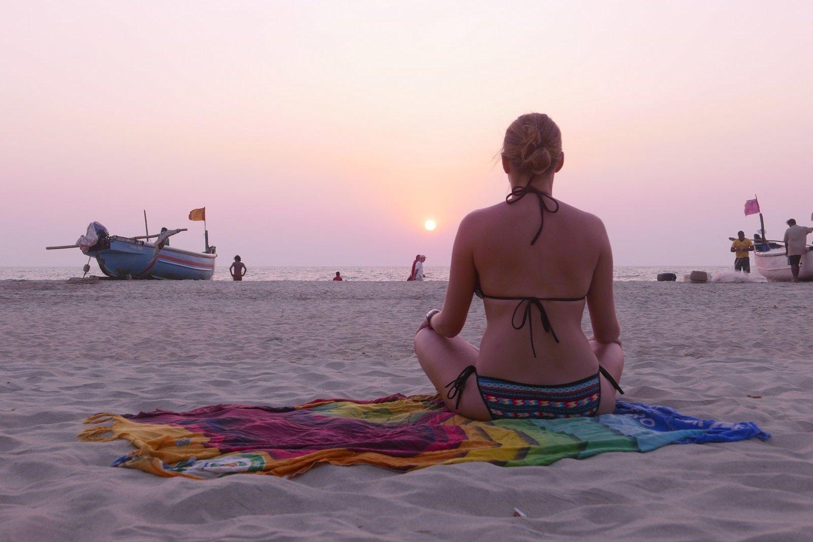 Méditation face au coucher de soleil sur la plage d'Arambol à Goa