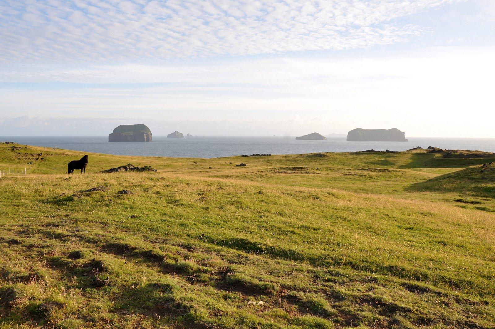 On aperçoit l'île de Surtsey au loin, cachée par les autres îles de l'archipel Vestmann
